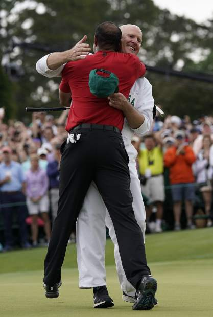 Tiger Woods reacts with his caddie Joe LaCava as he wins the Masters golf tournament Sunday, April 14, 2019, in Augusta, Ga. (AP Photo/David J. Phillip)