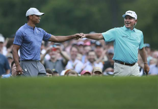 Tiger Woods and Fred Couples exchange a fist bump after they both hit their tee shots close to the cup on the par-3 No. 12 hole during a practice round for the Masters golf tournament in Augusta, Ga., Monday, April 8, 2019. (Curtis Compton/Atlanta Journal-Constitution via AP)