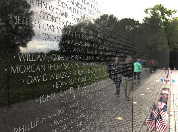 Names of the fallen are etched into the black granite walls of the Vietnam Veteran Memorial.