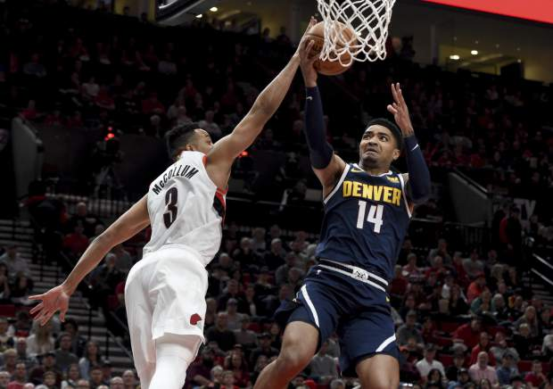 Denver Nuggets guard Gary Harris, right, drives to the basket on Portland Trail Blazers guard CJ McCollum during the first half of an NBA basketball game in Portland, Ore., Sunday, April 7, 2019. (AP Photo/Steve Dykes)