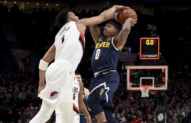 Portland Trail Blazers guard Evan Turner, left, blocks the shot of Denver Nuggets guard Isaiah Thomas at the end of the first quarter of an NBA basketball game in Portland, Ore., Sunday, April 7, 2019. (AP Photo/Steve Dykes)