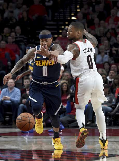 Denver Nuggets guard Isaiah Thomas, left, knocks the ball away from Portland Trail Blazers guard Damian Lillard during the first half of an NBA basketball game in Portland, Ore., Sunday, April 7, 2019. (AP Photo/Steve Dykes)