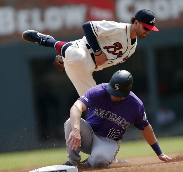Colorado Rockies' Mark Reynolds (12) is forced out at second base by Atlanta Braves shortstop Dansby Swanson (7) on a Charlie Blackmon ground ball in the seventh inning of a baseball game Sunday, April 28, 2019, in Atlanta. The Braves won 8-7. (AP Photo/John Bazemore)