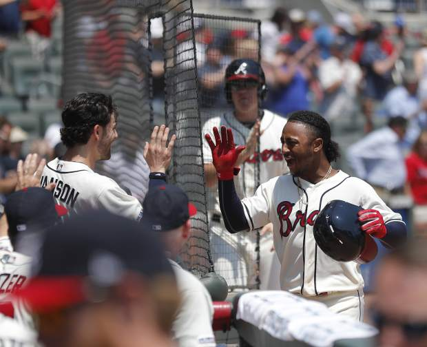Atlanta Braves' Ozzie Albies, right, celebrates with Dansby Swanson (7) after hitting a solo-home run in the first inning of a baseball game against the Colorado Rockies Sunday, April 28, 2019, in Atlanta. (AP Photo/John Bazemore)