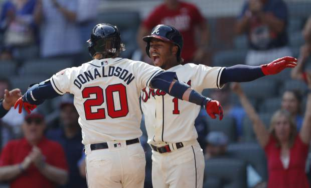 Atlanta Braves third baseman Josh Donaldson (20) celebrates with Ozzie Albies after hitting a three-run home run in the eighth inning of a baseball game against the Colorado Rockies, Sunday, April 28, 2019, in Atlanta. (AP Photo/John Bazemore)