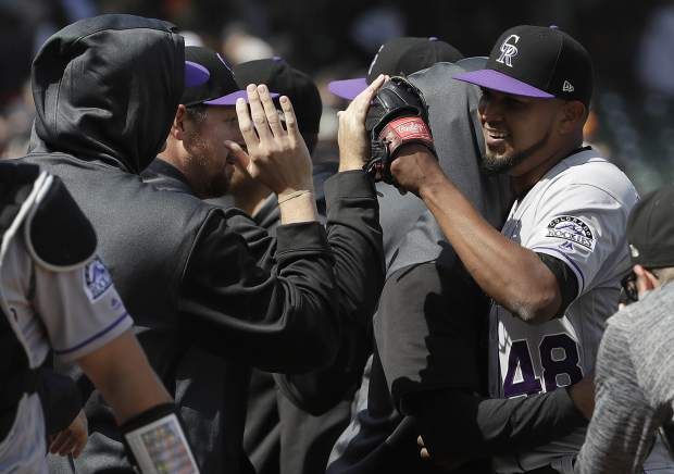 Colorado Rockies pitcher German Marquez, right, celebrates with teammates after they defeated the San Francisco Giants in a baseball game in San Francisco, Sunday, April 14, 2019. (AP Photo/Jeff Chiu)