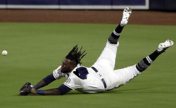 San Diego Padres center fielder Franmil Reyes misses the catch of a double hit by Colorado Rockies' Ian Desmond during the second inning of a baseball game Monday, April 15, 2019, in San Diego. (AP Photo/Gregory Bull)