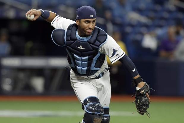 Tampa Bay Rays catcher Michael Perez fields a bunt by Colorado Rockies' Garrett Hampson during the third inning of a baseball game Monday, April 1, 2019, in St. Petersburg, Fla. Hampson was out at first when he ran out of the runners lane. (AP Photo/Chris O'Meara)