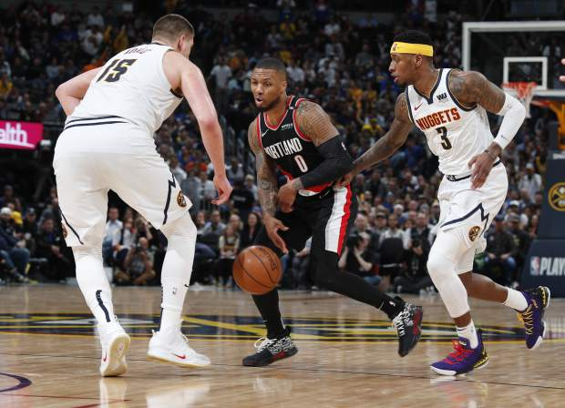 Portland Trail Blazers guard Damian Lillard, center, loses control of the ball as Denver Nuggets center Nikola Jokic, left, and forward Torrey Craig defend in the second half of Game 1 of an NBA basketball second-round playoff series, Monday, April 29, 2019, in Denver. The Nuggets won 121-113. (AP Photo/David Zalubowski)