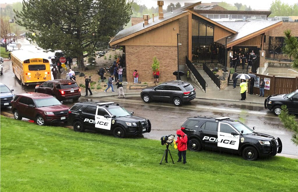 Police and others are seen outside STEM School Highlands Ranch, a charter middle school in the Denver suburb of Highlands Ranch, Colo., after a shooting Tuesday, May 7, 2019. Authorities said several people were injured and a few suspects were in custody. (AP Photo/David Zalubowski)