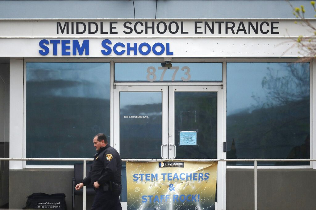 A Douglas County, Colo., Sheriffs Department deputy walks past the doors to the STEM Highlands Ranch school early Wednesday, May 8, 2019, in Highlands Ranch, Colo. Two high school students used at least two handguns in a fatal Tuesday shooting at the charter school authorities said Wednesday. (AP Photo/David Zalubowski)