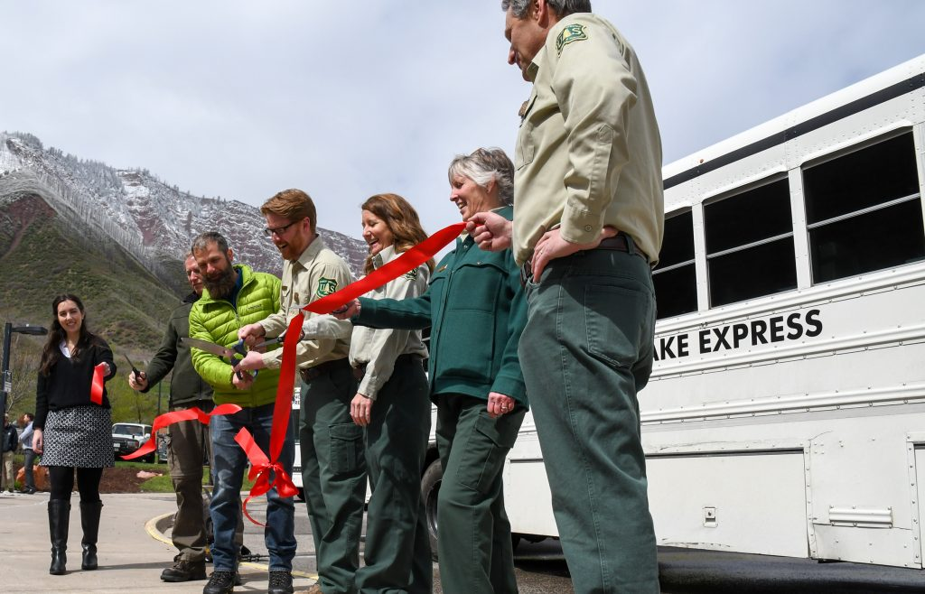 Former Glenwood Springs Mayor Mike Gamba, newly elected mayor Jonathan Godes, and representatives of the White River National Forest Service cut the ribbon during the ceremony celebrating the opening of the new Hanging Lake Welcome Center and shuttle service on Wednesday morning.