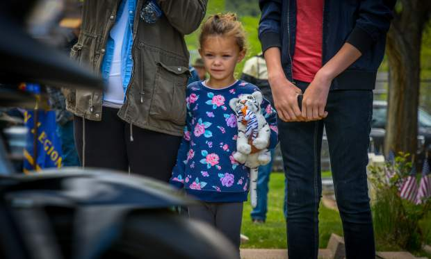 A young girl watches as the Western Slope Memorial Riders leave Rosebud Cemetery during the closing of the 2019 Memorial Day ceremony on Monday morning.