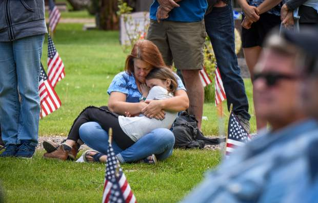 A woman and child embrace during the 2019 Memorial Day ceremony held at Rosebud Cemetery in Glenwood Springs on Monday.
