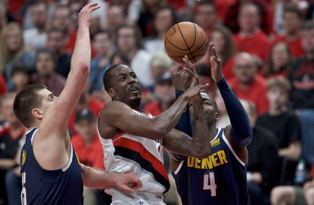 Portland Trail Blazers forward Al-Farouq Aminu, center, shoots between Denver Nuggets forward Paul Millsap, right, and center Nikola Jokic, left, during the first half of Game 4 of an NBA basketball second-round playoff series Sunday, May 5, 2019, in Portland, Ore. (AP Photo/Craig Mitchelldyer)