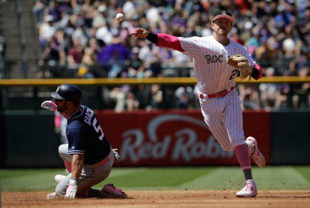 Colorado Rockies third baseman Ryan McMahon, right, forces out San Diego Padres baserunner Greg Garcia, left, at second base in the third inning of a baseball game in Denver, Sunday, May 12, 2019.(AP Photo/Joe Mahoney)