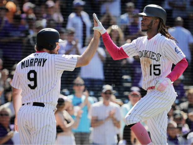 Colorado Rockies' Daniel Murphy (9) congratulates teammate Raimel Tapia (15) after Tapia hit a home run that also scored him in the seventh inning of a baseball game against the San Diego Padres in Denver, Sunday, May 12, 2019. (AP Photo/Joe Mahoney)