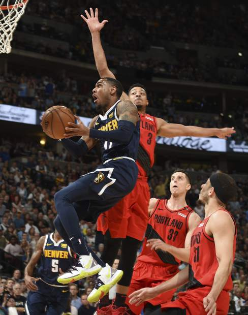 Denver Nuggets guard Monte Morris, front, drives to the rim past Portland Trail Blazers guard CJ McCollum, back left, forward Zach Collins and guard Seth Curry in the first half of Game 7 of an NBA basketball second-round playoff series Sunday, May 12, 2019, in Denver. (AP Photo/John Leyba)
