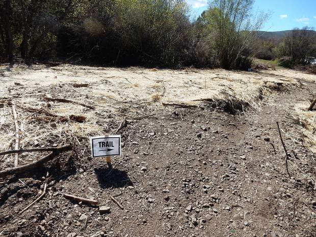 A sign placed by Roaring Fork Mountain Bike Association marks the way on the popular Lower Monte Carlo Trail through a dended swath cut to bury a water pipe.