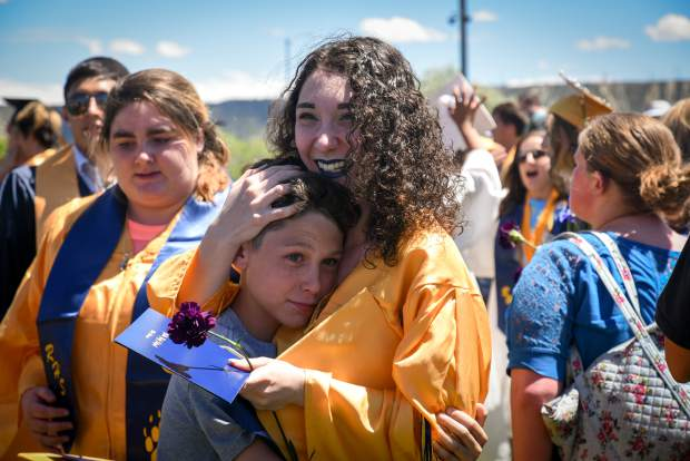 A RIfle High School graduate is embraced by family following the commencement ceremony on Saturday afternoon.