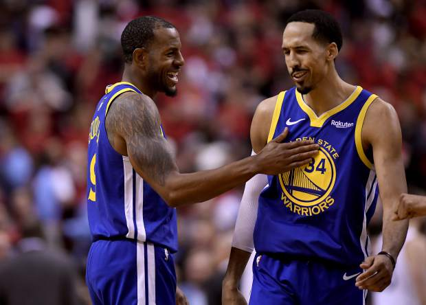 Golden State Warriors forward Andre Iguodala (9) and teammate Shaun Livingston (34) celebrate their win against the Toronto Raptors following the second half of Game 2 of basketball's NBA Finals, Sunday, June 2, 2019, in Toronto. (Frank Gunn/The Canadian Press via AP)