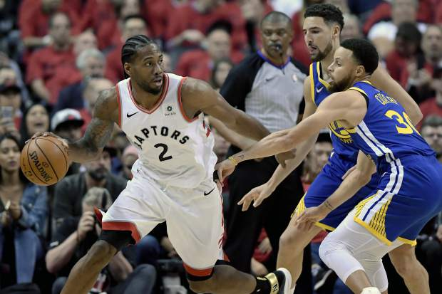 Toronto Raptors forward Kawhi Leonard (2) looks for a way out under pressure from Golden State Warriors guard Stephen Curry (30) and teammate Klay Thompson (11) during the first half of Game 2 of basketball's NBA Finals, Sunday, June 2, 2019, in Toronto. (Frank Gunn/The Canadian Press via AP)