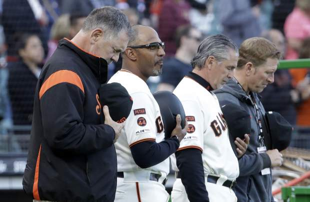 From left to right, San Francisco Giants' manager Bruce Bochy observes a moment of silence for slain Sacramento Police officer Tara O'Sullivan next to coaches Jose Alguacil and Ron Wotus before a baseball game against the Colorado Rockies in San Francisco, Monday, June 24, 2019. (AP Photo/Jeff Chiu)
