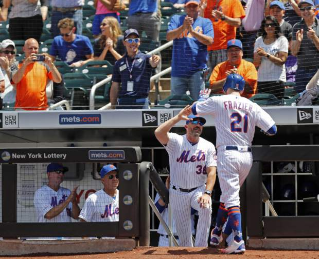 New York Mets manager Mickey Callaway (38) congratulates Todd Frazier (21) after Frazier hit a three-run, home run during the first inning a baseball game against the Colorado Rockies, Sunday, June 9, 2019, in New York. (AP Photo/Kathy Willens)