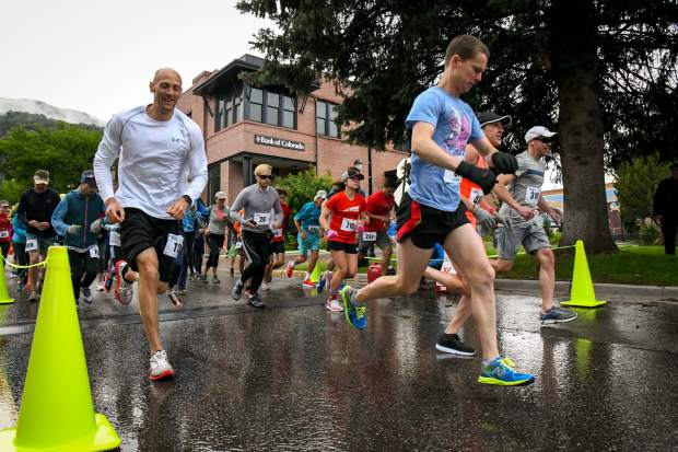 Runners take off at the starting line of the 10K Strawberry Shortcut near Ninth and Grand on a wet and cold Sunday morning.