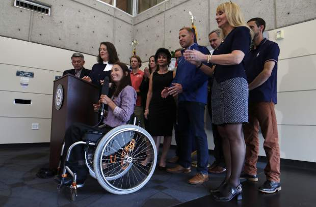 As U.S. Rep. Diana DeGette, D-Colo., and U.S. Sen. Cory Gardner, R-Colo., back, look on, Sarah Will of Arvada, Colo., a 12-time gold medalist in skiing in the Paralympics, speaks during a news conference to announce a plan to introduce legislation aimed at reforming the U.S. Olympic Committee Monday, June 17, 2019, in Denver. Nearly a dozen Olympic athletes were on hand to lend their support to the measure, which DeGette plans to introduce this week. (AP Photo/David Zalubowski)