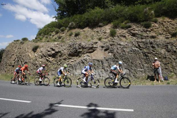 A spectator takes a snapshot of the pack riding during the tenth stage of the Tour de France cycling race over 217 kilometers (135 miles) with start in Saint-Flour and finish in Albi, France, Monday, July 15, 2019. (AP Photo/ Christophe Ena)