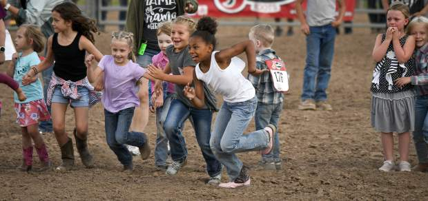It's a mad dash as the Calf Scramble takes to the outdoor arena at the Garfield County Fairgrounds Monday in Rifle.