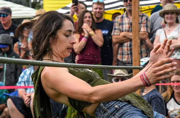 A contestant focuses even in a downpour during the limbo competition at the 48th Annual Carbondale Mountain Fair on Saturday afternoon.