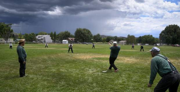 Star BBC of Silt's Michael Hixson belts the ball over the infield as a rain storm passes to the south of Silt during thrid-inning action.