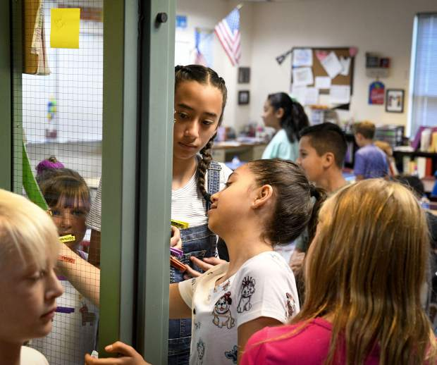 Fifth graders in Shannon McKee's class check into the classroom Monday during the first day of school for Garfield County School District No. Re-2.