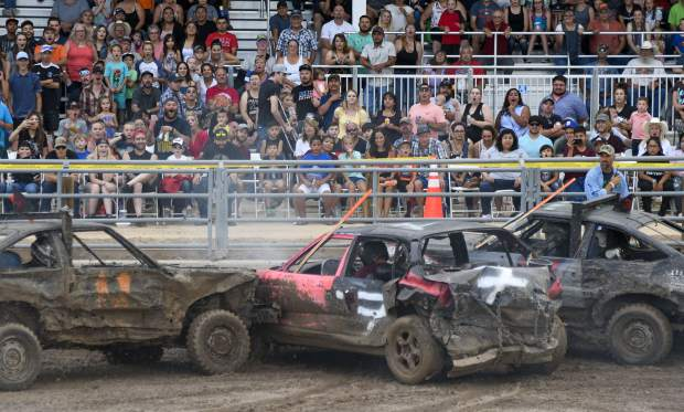 The crowd reacts as three cars collide as competitors try to knock each other out last Saturday in the outdoor arena.