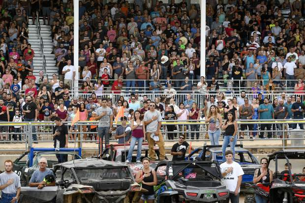 Competitors and fans salute the flag before the start of the fan favorite Demolition Derby Saturday night at the Garfield County Fairgrounds.