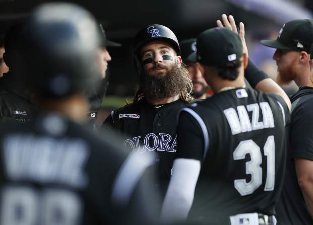 Colorado Rockies' Charlie Blackmon, center, is congratulated by teammates as he returns to the dugout after scoring on a single by Raimel Tapia off Arizona Diamondbacks starting pitcher Merrill Kelly in the first inning of a baseball game Monday, Aug. 12, 2019, in Denver. (AP Photo/David Zalubowski)