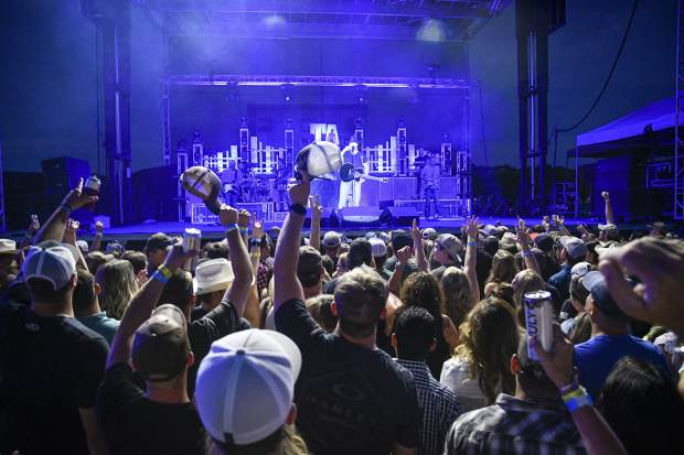 The crowd tips its hats and raise a toast with Trace Adkins as he peforms Friday night in Rifle.