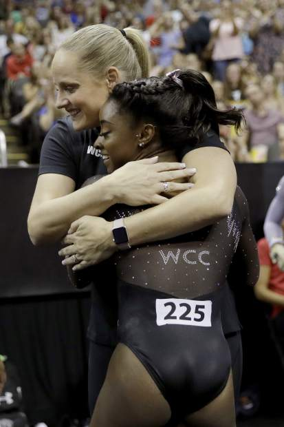 Simone Biles hugs her coach Cecile Canqueteau-Landi after competing in the floor exercise during the senior women's competition at the 2019 U.S. Gymnastics Championships Sunday, Aug. 11, 2019, in Kansas City, Mo. (AP Photo/Charlie Riedel)