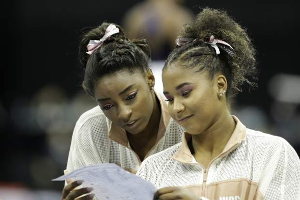 Simone Biles, left, and Jordan Chiles look over a rotation schedule during practice for the senior women's competition at the 2019 U.S. Gymnastics Championships Sunday, Aug. 11, 2019, in Kansas City, Mo. (AP Photo/Charlie Riedel)