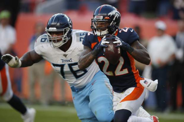 Denver Broncos defensive back Kareem Jackson (22) intercepts a pass as Tennessee Titans offensive guard Rodger Saffold chases during the second half of an NFL football game Sunday, Oct. 13, 2019, in Denver. (AP Photo/David Zalubowski)